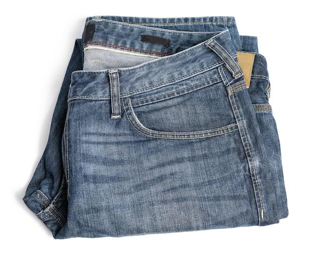 白い背景の上の折り畳まれた青いメンズジーンズ、上面図