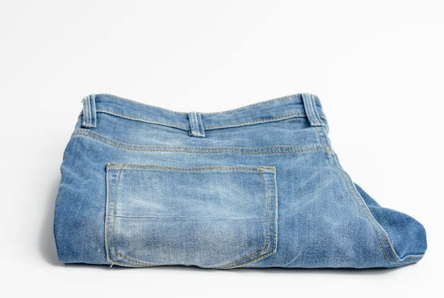 Folded blue men's jeans on a white background, top view