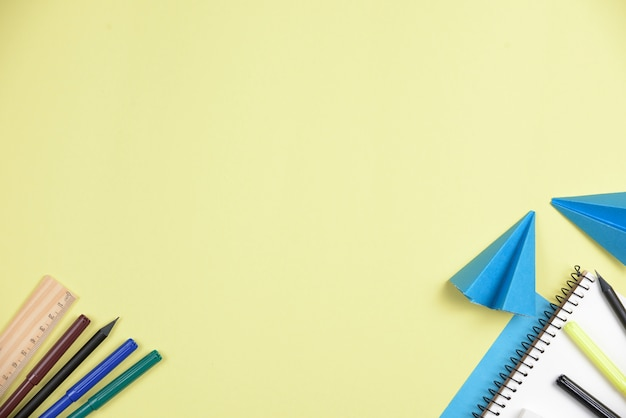 Сложенные синие бумаги с офисными канцелярскими на желтом фоне с пространством для написания текста