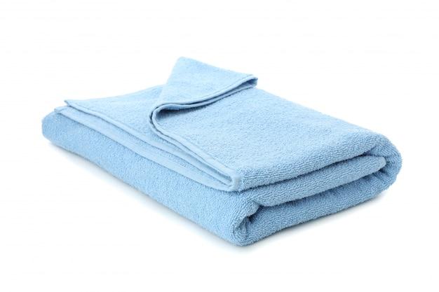 白い背景に分離された青いタオルを折り、クローズアップ