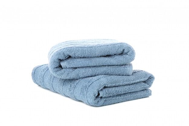 Folded blue towels isolated on white background, close up