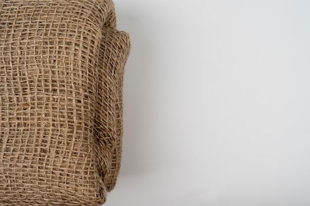 白い背景の折り畳まれた黄麻布生地しわくちゃの生地の質感ナチュラルベージュジュート生地