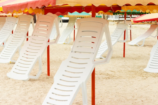 Folded chaise lounges and umbrellas on the sandy beach