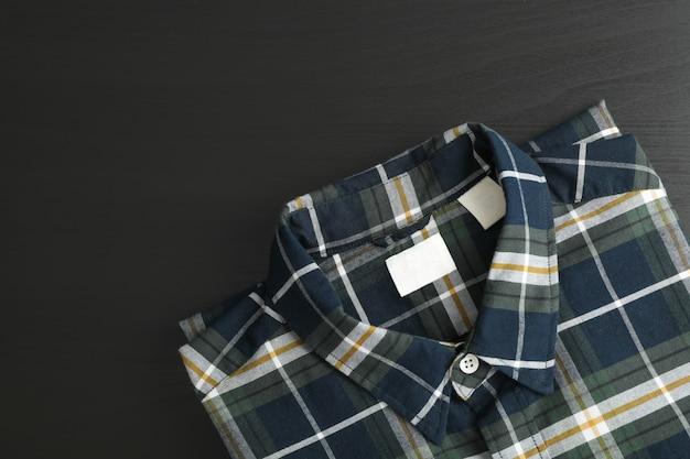 블랙 테이블에 접힌 된 체크 무늬 셔츠, 텍스트를위한 공간