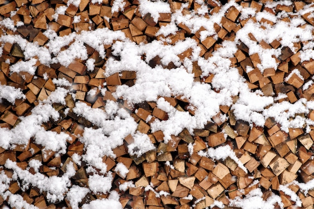 Folded chopped firewood covered with snow in winter