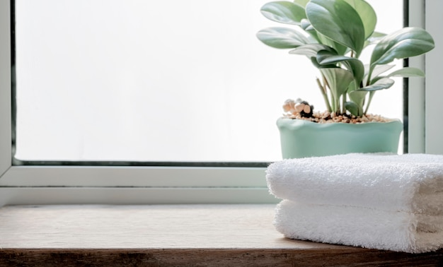 Folded clean towels with houseplant on wooden table. copy space.