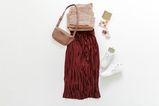 女性のための折り畳まれた服は、都会の基本的な服をファッションします。女性の春の外観秋の服ブルゴーニュスカートベージュのセーター白い靴スニーカーバッグと白い背景の上の化粧品を構成する上面図フラットレイ。