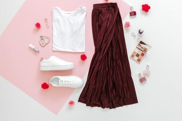 女性のための折り畳まれた服は、アクセサリーの花で都会の基本的な服をファッションし、ピンクの背景に化粧品を構成します。女性の春の外観の夏の服のスカートの靴のスニーカーの基本的なtシャツバッグ。上面図。