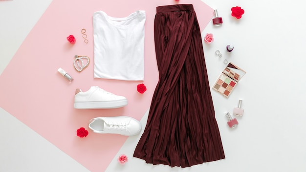 女性のための折り畳まれた服は、アクセサリーの花で都会の基本的な服をファッションし、ピンクの背景に化粧品を構成します。女性の春の外観の夏の服のスカートの靴スニーカーの基本的なtシャツ。長いウェブバナー。