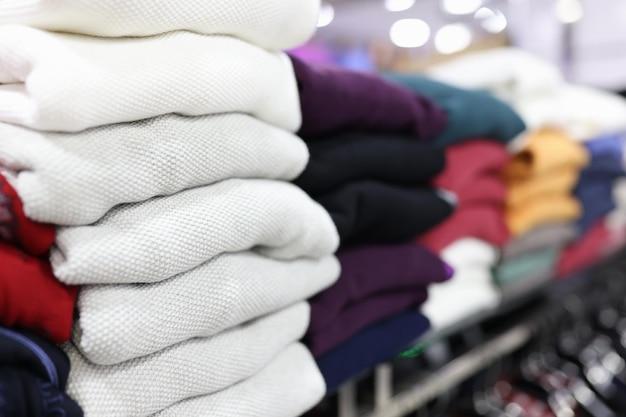 店の棚のクローズアップブラックフライデーのコンセプトに横たわっている折り畳まれた服