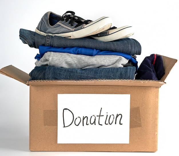 Folded clothes and shoes in a brown paper box