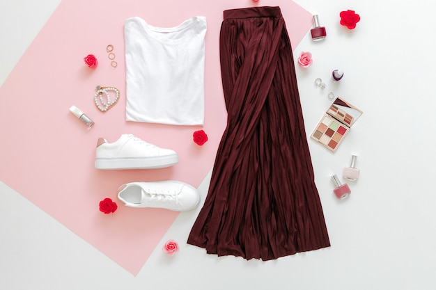 Folded clothes for women fashion urban basic outfit with accessories flowers make up cosmetics on pink background.female spring look summer outfit skirt shoes sneakers basic tshirt bag. top view.