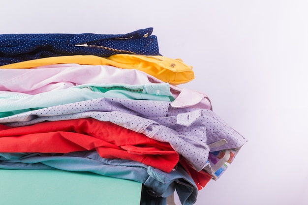 Folded colorful pants and jeans. stack of bright female trousers. close up.