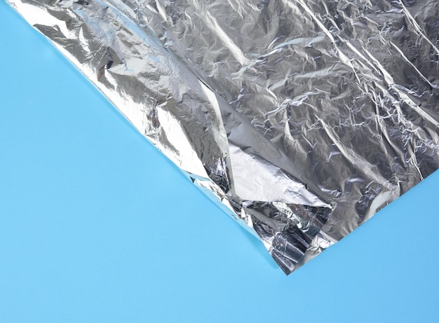 Folded corner of gray food foil on brown surface, top view