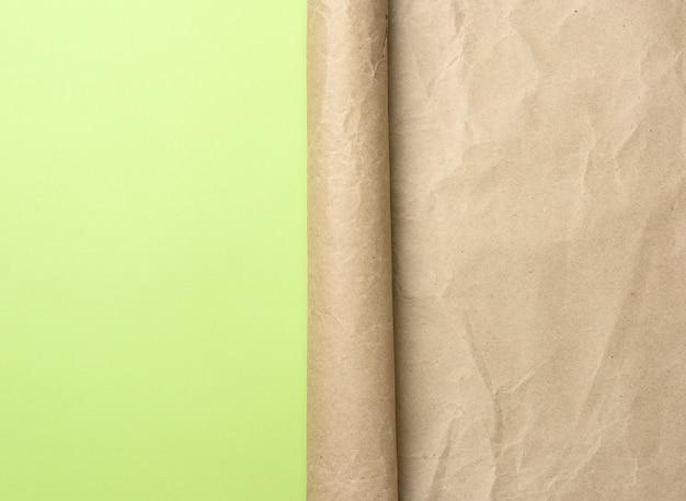 Сложенный угол рулона коричневой бумаги на зеленом фоне, место для надписи