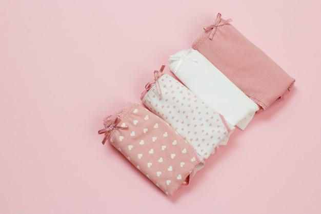 분홍색 배경에 다른 색상의 접힌 면 팬티. 여성 속옷 세트입니다. 평면도.