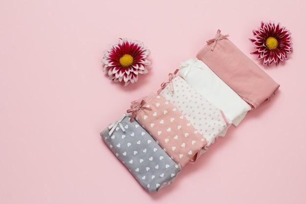 분홍색 배경에 꽃 봉오리가 있는 다른 색상의 접힌 면 팬티. 여성 속옷 세트입니다. 평면도.
