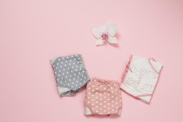 분홍색 배경에 난초 꽃 봉오리가 있는 다른 색상의 접힌 면 팬티. 여성 속옷 세트입니다. 평면도.