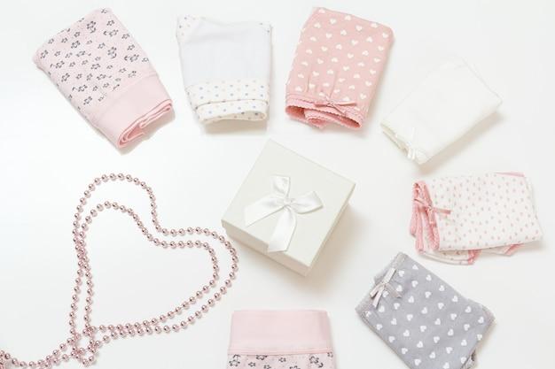 さまざまな色の折り畳まれた綿のパンティー、ギフトボックス、白い表面のビーズ