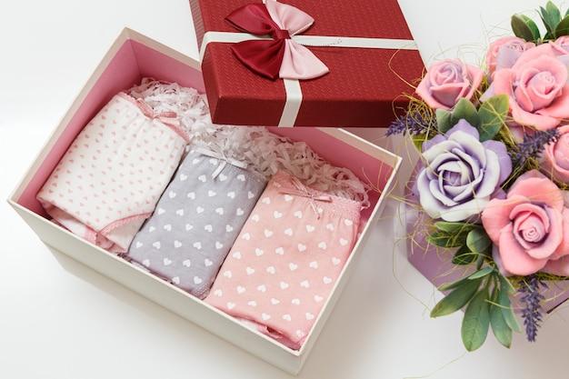 白い背景に造花が付いたボックスにさまざまな色の折り畳まれた綿のパンティー。女性下着セット。上面図。