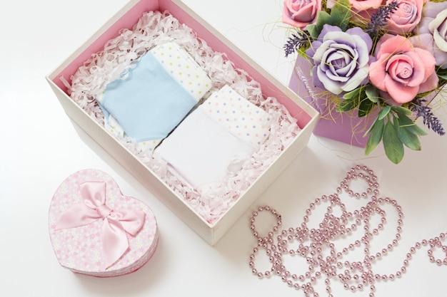 白い表面に造花が付いた箱にさまざまな色の折り畳まれた綿のパンティー