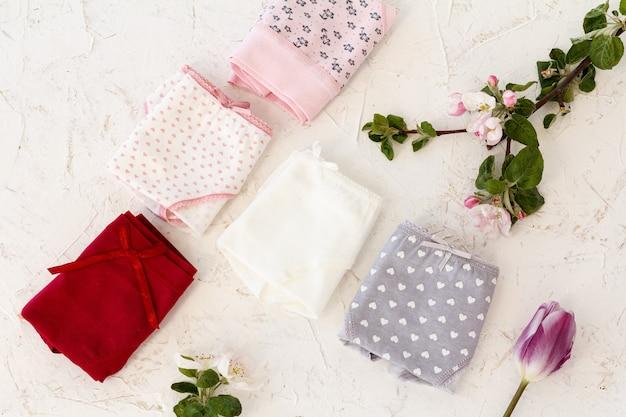 흰색 바탕에 튤립과 사과나무 꽃이 있는 접힌 면 팬티. 여성 속옷 세트입니다. 평면도.