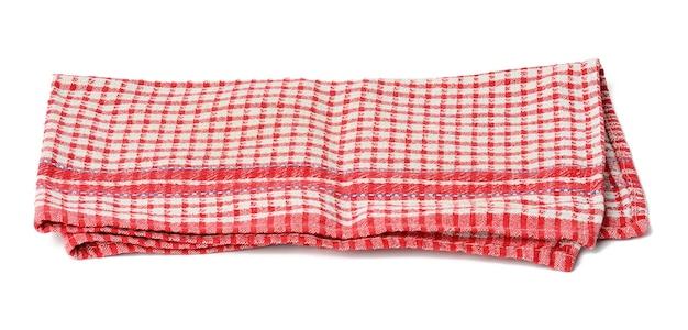 Сложенная хлопковая красно-белая клетчатая салфетка на белом фоне