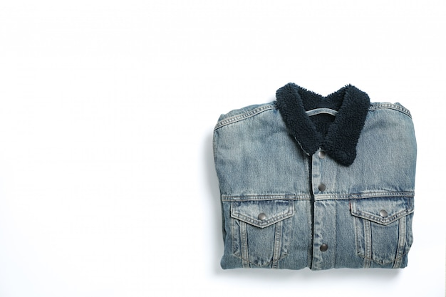 Folded denim jacket on white background, space for text