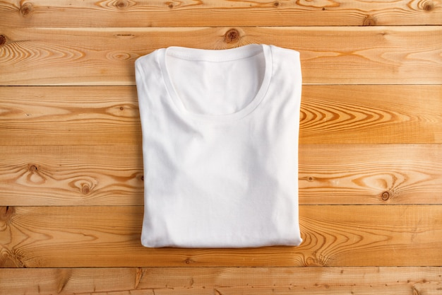 Folded female white t-shirt on a wooden background