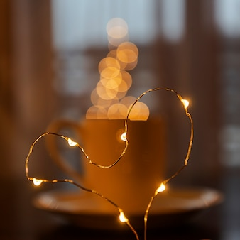 Folded from a garland heart on the  of a blurred cup of coffee or tea, a steam from garland blurred bokeh. festive mood. blurred. defocused.