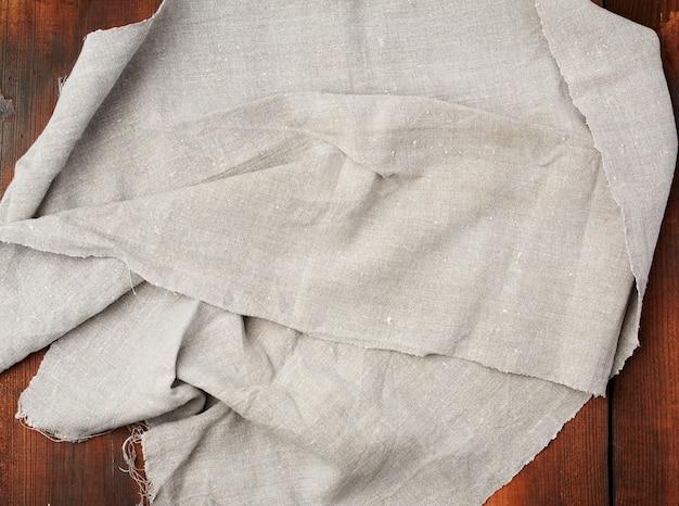Folded gray linen towel on wooden