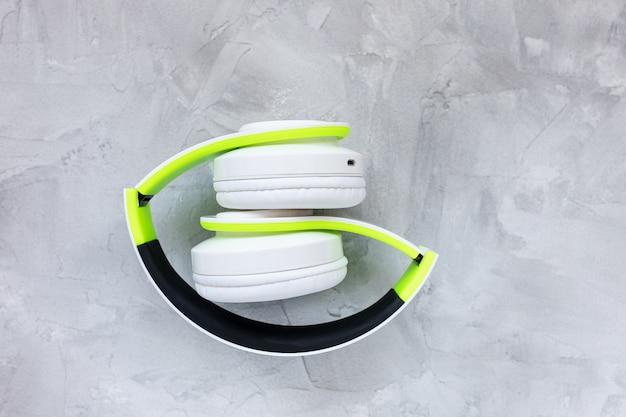 灰色の背景に折りたたまれた緑と白のヘッドフォン