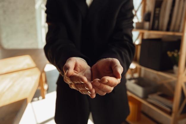 접힌 손. 사무실에서 일하는 백인 남성 손을 닫습니다.