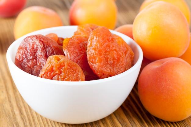 Сложенная в белую миску кураги, стоит на деревянной доске, на которой лежат спелые и сочные абрикосы нового урожая, крупный план
