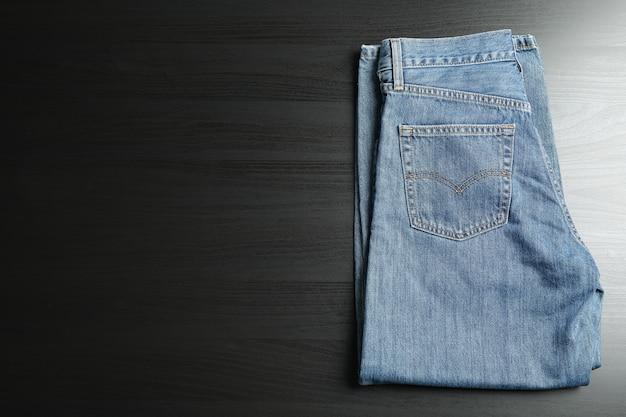黒いテーブルに折り畳まれたジーンズ、テキスト用のスペース