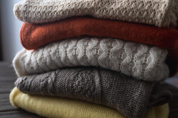 折りたたまれた暖かいセーターが積み重ねられています。さまざまなニットパターン。秋または冬の背景。