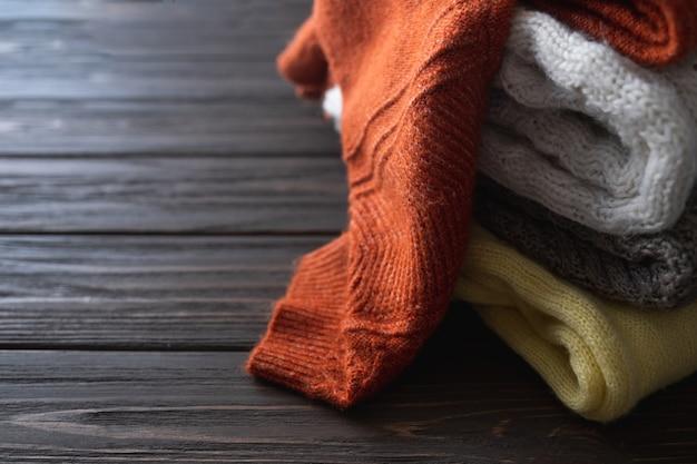 Сложенные вязаные теплые свитера-полууловы или пледы осенне-зимняя одежда место для текста