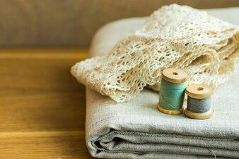 Сложенная льняная ткань, кружевные ленты, нитки, деревянные катушки на столе
