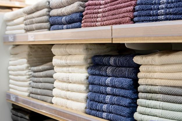 Сложенные разноцветные полотенца на полках. аккуратно сложенная одежда. стеллаж с теплой одеждой. хлопковые полотенца аккуратно сложены