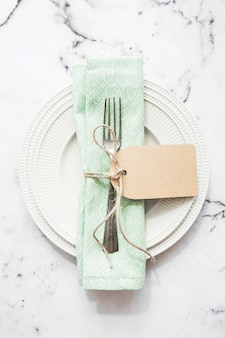 Folded napkin and fork tied with string and blank tag on white ceramic plate