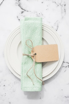 Folded napkin tied with blank tag on an empty flat round plate