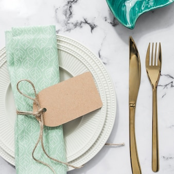 Folded napkin tied with blank tag on plate and cutlery on marble textured background