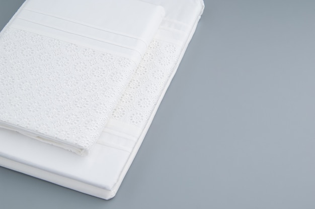 Folded new tablecloth with embroidered patterns on a gray background, top view