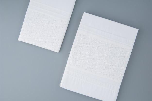 회색 배경에 자수 패턴이 있는 접힌 새 식탁보, 위쪽