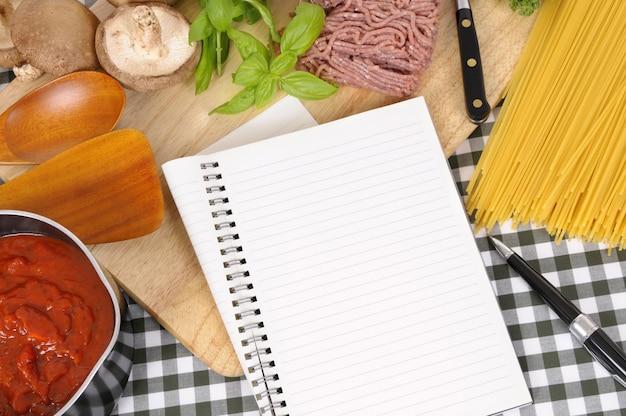 Сложенный ноутбук с ингредиентами для спагетти болоньезе
