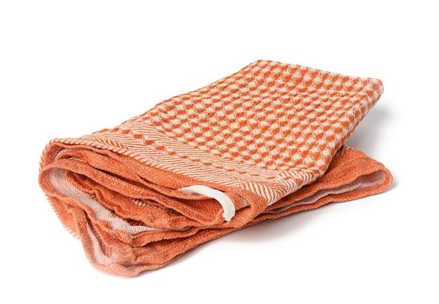 Сложенное оранжевое льняное полотенце на белом фоне, вид сверху