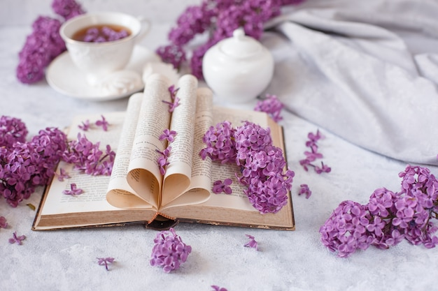 Folded pages of an old french book with branches of blooming lilac and flower petals