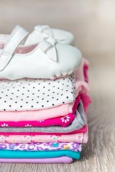 ピンクと白の折り畳まれたボディースーツと靴