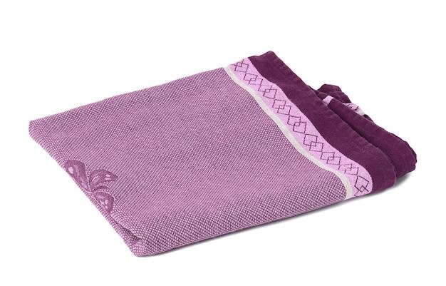 Сложенное фиолетовое льняное полотенце на белом фоне, вид сверху