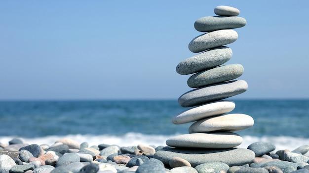해변에 매끄러운 돌의 접힌 피라미드. 휴가의 휴식과 휴식